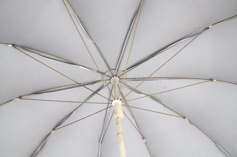 El superficie inferior de un paraguas gris claro imagenes de archivo