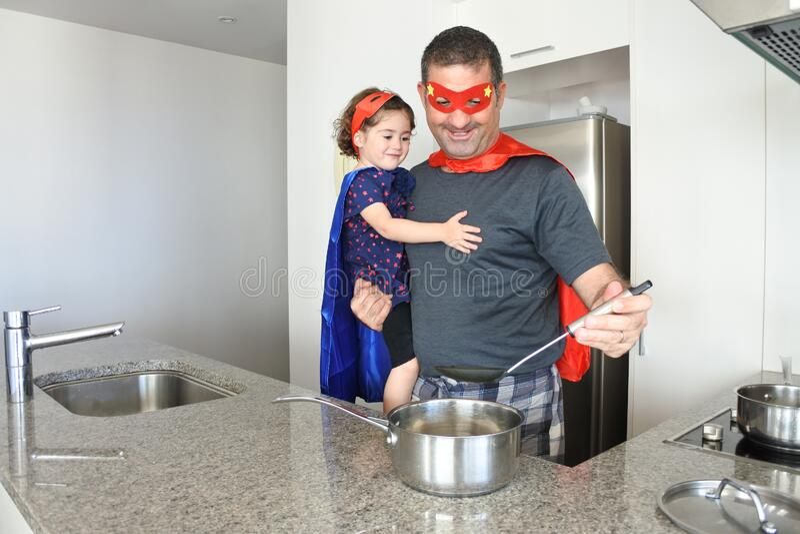 El superhéroe padre e hija cocinando juntos imagenes de archivo