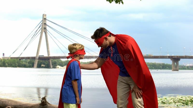 El superhombre inspira al hijo-super héroe que gane, la ayuda paternal, consejo para el hombre real fotografía de archivo