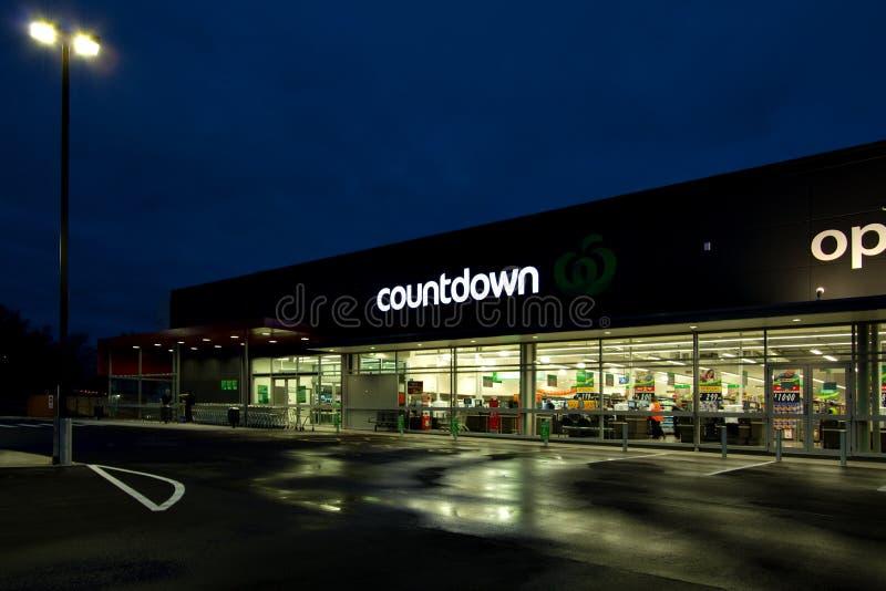 El supermercado del ultramarinos de la cuenta descendiente se encendió para arriba en noche lluviosa imágenes de archivo libres de regalías