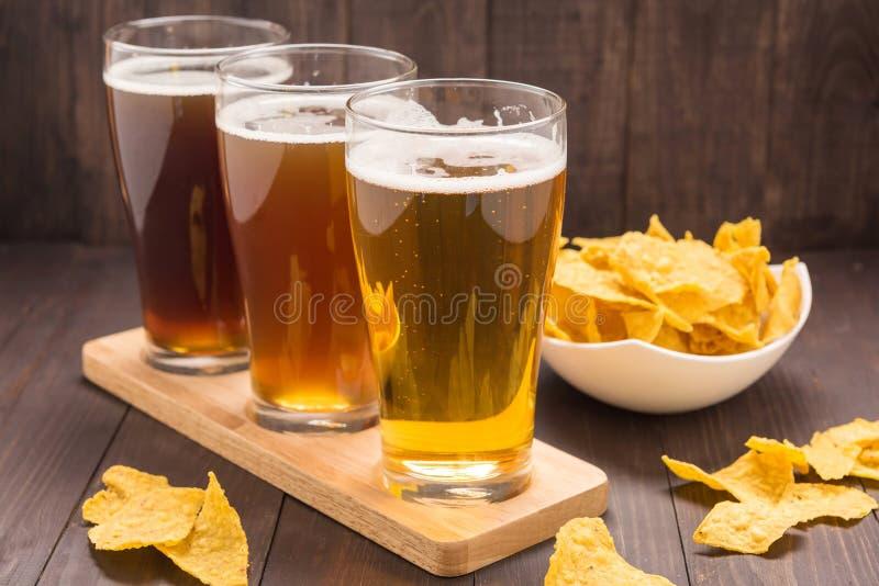 El surtido de vidrios de cerveza con nachos salta en una tabla de madera foto de archivo