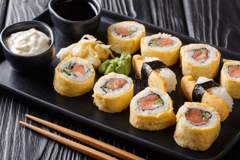 El sushi japonés fijó el rollo con el arroz, la tortilla, el queso, los salmones y el aguacate servidos con las salsas, el wasabi fotografía de archivo libre de regalías