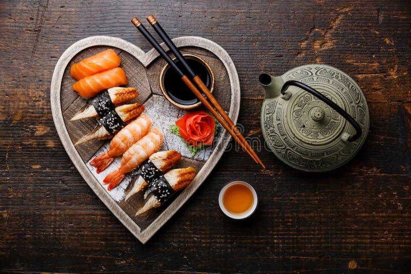 El sushi y el té sirvieron en la bandeja de madera de la forma del corazón imagen de archivo