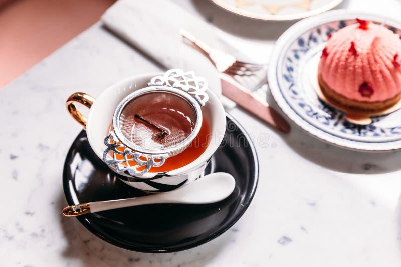 El té caliente filtrado de Apple sirvió en taza del vintage de la porcelana con cremas batidas se apelmaza en la tabla superior d imagen de archivo libre de regalías