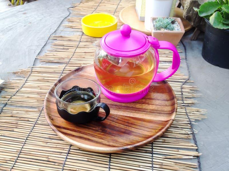 El té caliente se despliega en las esteras de bambú en la tabla como fondo fotos de archivo