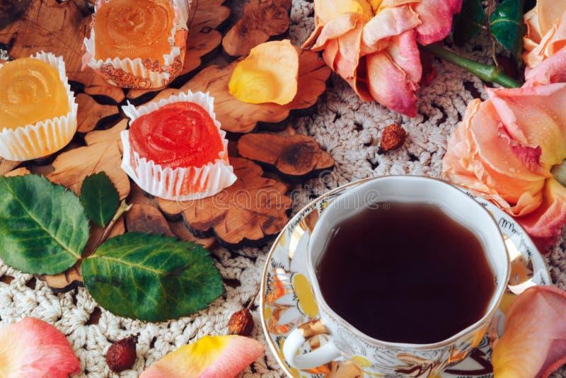 El té con la mermelada en la tabla es flores color de rosa imagen de archivo libre de regalías