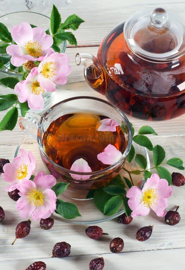 El té de la taza y de la tetera con la cadera subió las flores fotos de archivo libres de regalías