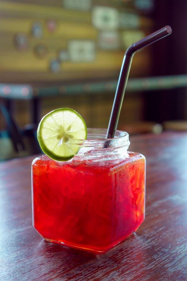 El té del limón en el vidrio del cubo con una paja que adorna con la cal en el café imagen de archivo