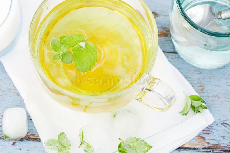 El té frío de la hoja de la menta fresca, acuña té con los cubos de hielo en una taza de cristal en una tabla de madera imagen de archivo