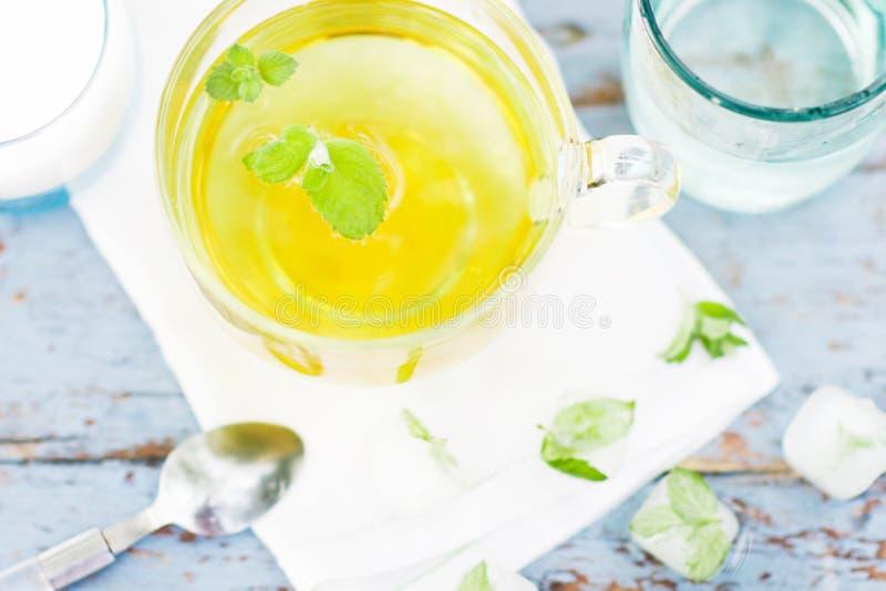 El té frío de la hoja de la menta fresca, acuña té con los cubos de hielo en una taza de cristal en una tabla de madera foto de archivo libre de regalías