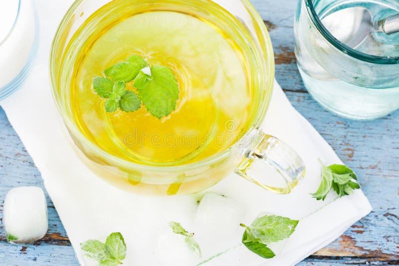 El té frío de la hoja de la menta fresca, acuña té con los cubos de hielo en una taza de cristal en una tabla de madera fotografía de archivo libre de regalías