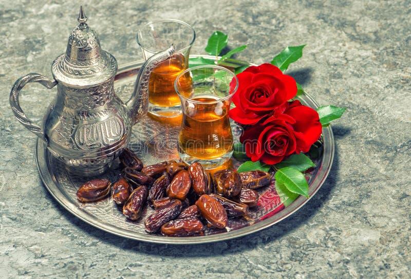 El té, las frutas de las fechas y la rosa del rojo florece Estafa oriental de la hospitalidad fotografía de archivo libre de regalías
