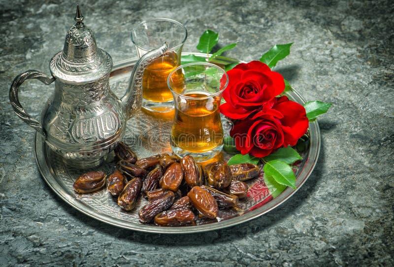 El té, las frutas de las fechas y la rosa del rojo florece Vin oriental de la hospitalidad fotos de archivo