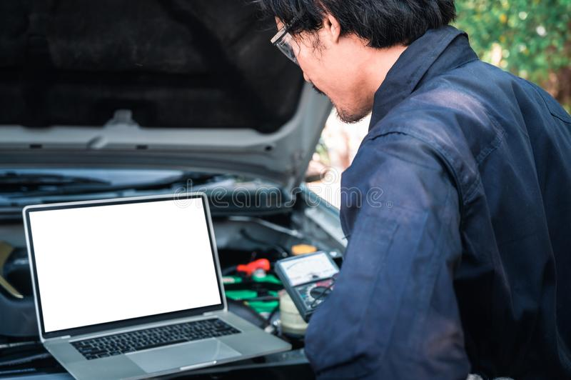 El técnico asiático analizar el gráfico del motor de coche en el ordenador portátil en el garaje el concepto de automotriz, repar imagen de archivo libre de regalías