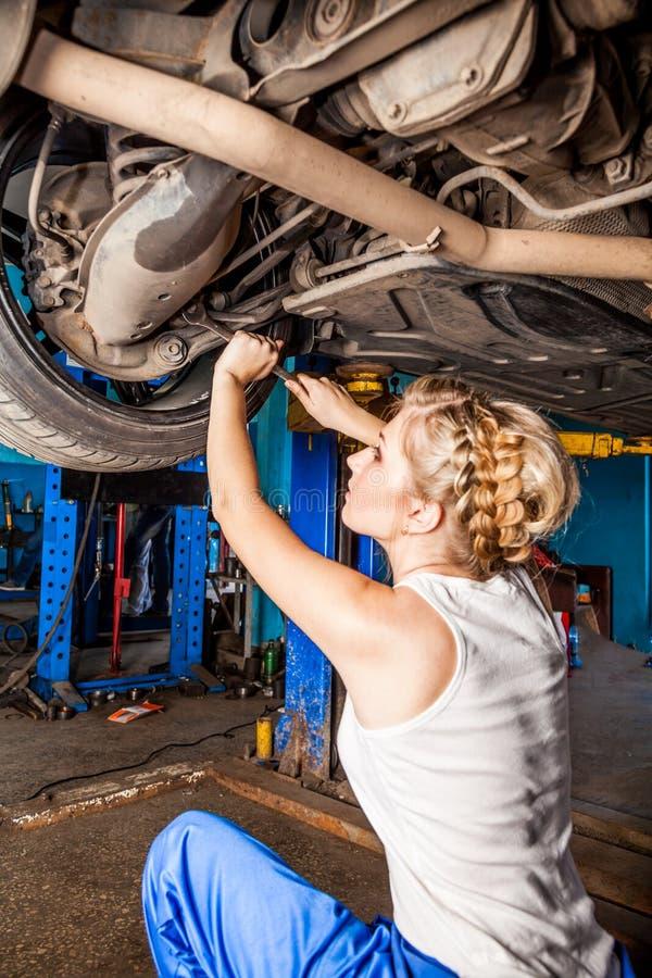 El técnico de sexo femenino substituye la rueda del vehículo en servicio fotos de archivo libres de regalías