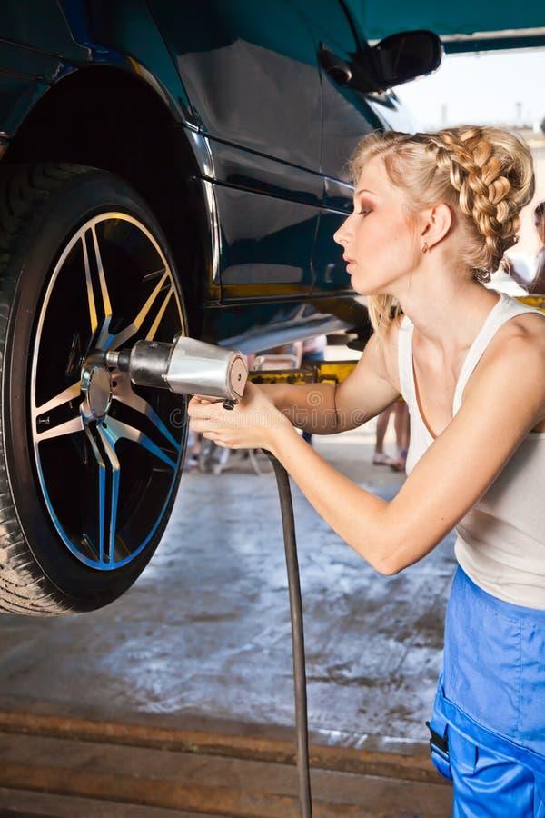 El técnico de sexo femenino substituye la rueda del vehículo en servicio foto de archivo libre de regalías