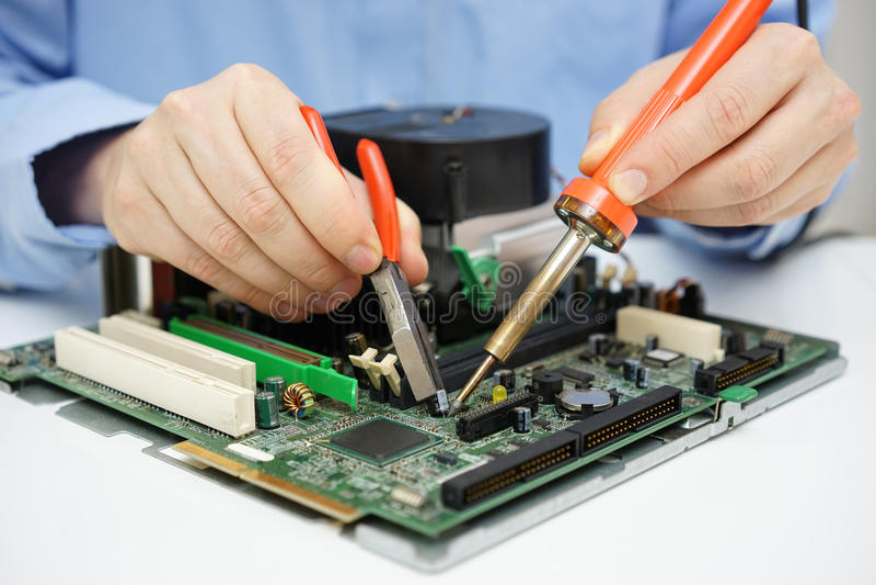 El técnico del ordenador está cambiando el condensador en la placa madre culpable imágenes de archivo libres de regalías