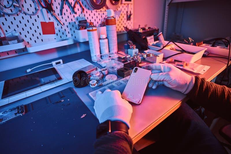 El técnico electrónico sostiene un smartphone moderno con un cuerpo quebrado que se sienta en una tabla en un taller de reparacio fotos de archivo libres de regalías