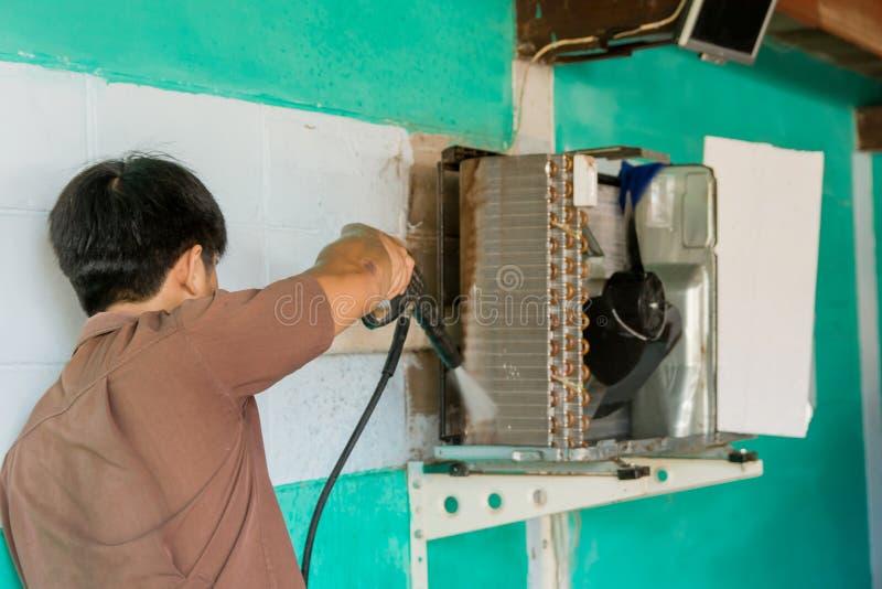 El técnico está manteniendo la reparación y los aires acondicionados Compresor limpio con la lavadora de alta presión foto de archivo libre de regalías