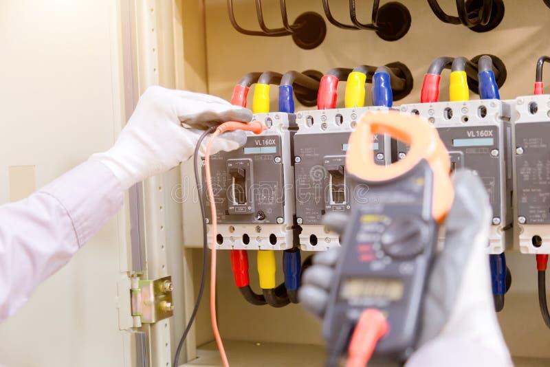 El técnico está midiendo voltaje o la corriente por el voltímetro en contr fotos de archivo
