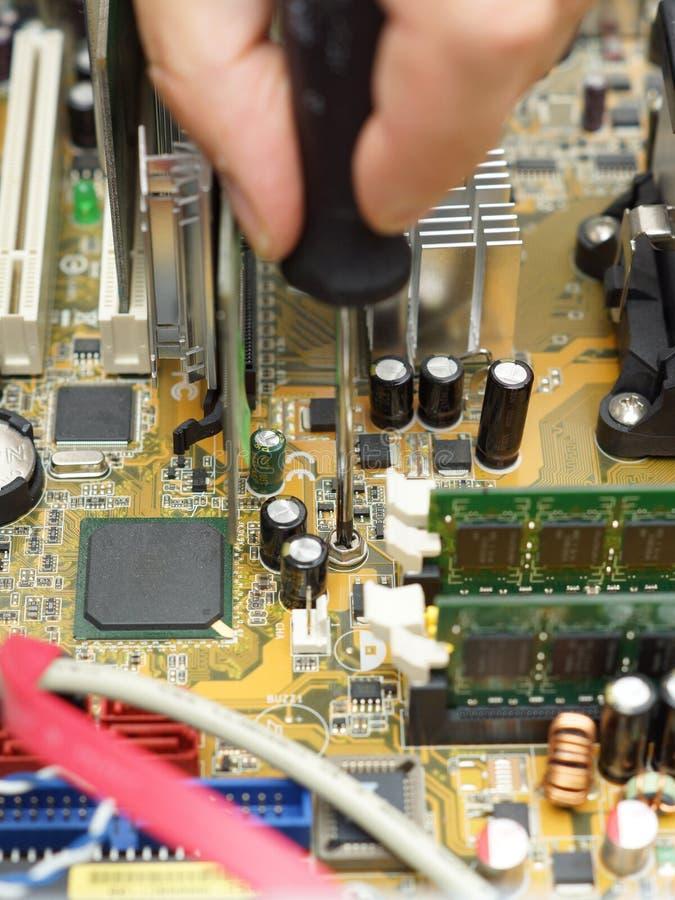 El técnico está reparando el ordenador usando el destornillador fotos de archivo