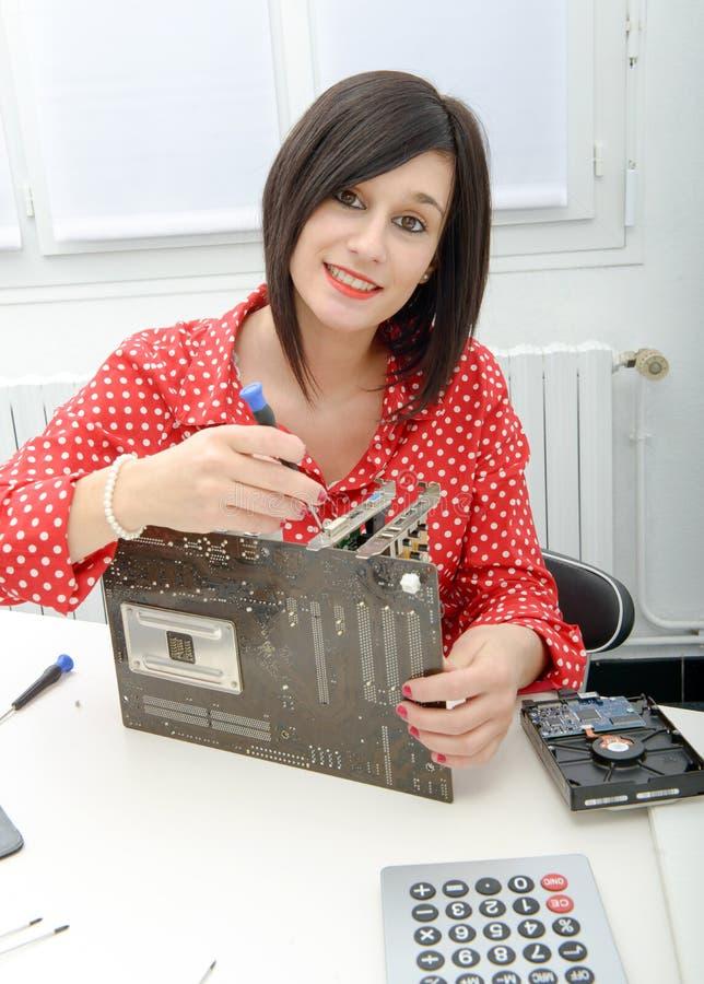 El técnico moreno de la mujer repara una placa madre fotografía de archivo
