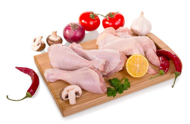 El tablero con las piernas de pollo y las alas crudas, verduras para cocinar es imagenes de archivo