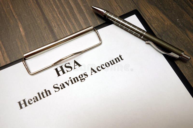 El tablero con tiene el cuenta de ahorros y pluma de la salud en el escritorio foto de archivo libre de regalías