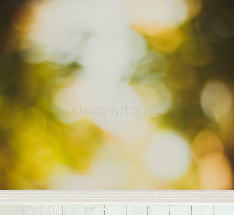 El tablero de la mesa de madera con la naturaleza verde fresca empañó el fondo fotografía de archivo