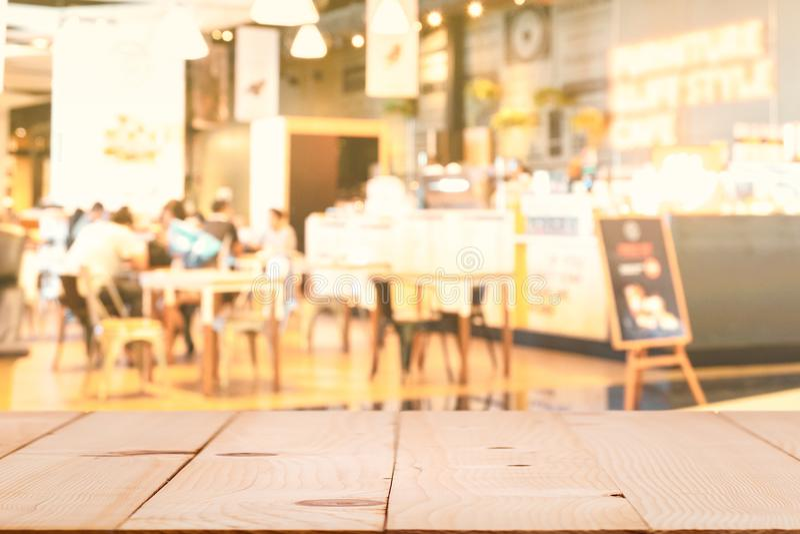 El tablero de la mesa de madera con la cafetería de la falta de definición o restaurante del café y la promoción firman, fondo ab imagen de archivo