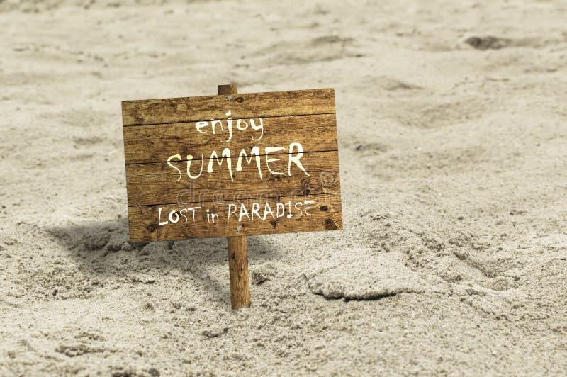 El tablero de madera pegado en la arena con el texto DISFRUTA DE VERANO PERDIÓ EN PARADISE imagen de archivo