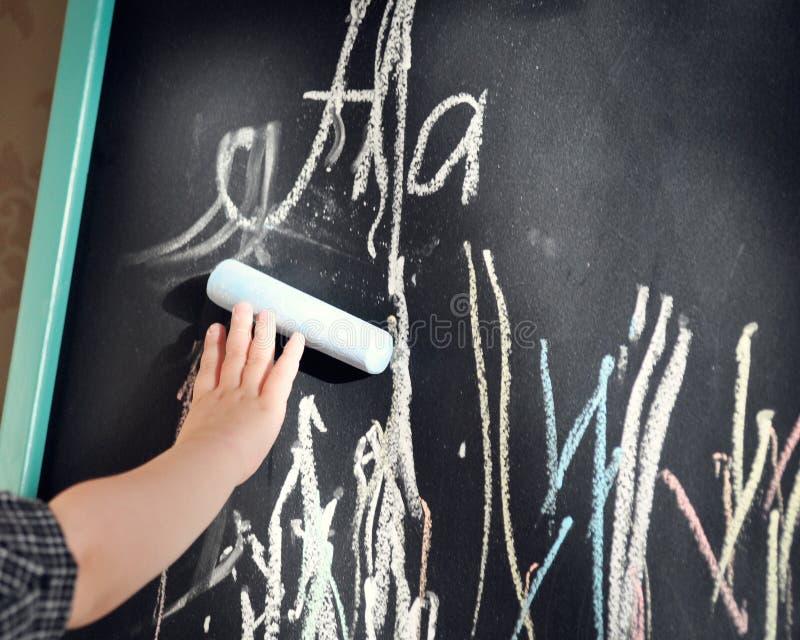 El tablero de tiza negro garabateó al niño pequeño coloreó los creyones Aprendizaje del alfabeto y preparación para la escuela foto de archivo
