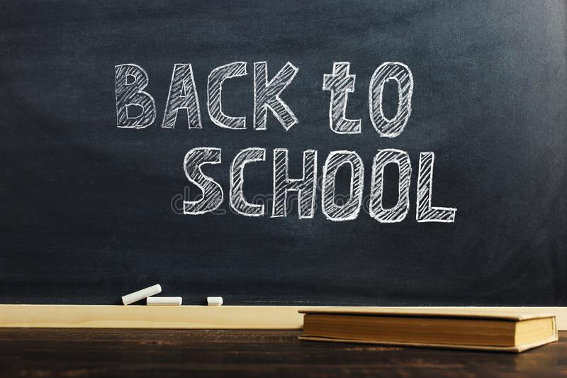 El tablero de tiza negro sobre la tabla de madera con el libro, esconde para el texto o el fondo para el tema de la escuela imagen de archivo libre de regalías