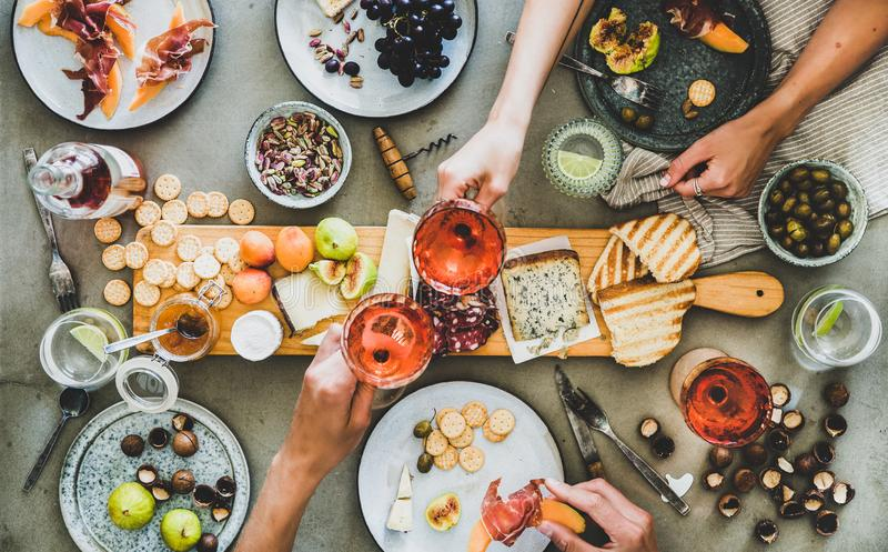 El tablero del Charcuterie y del queso, vino rosado, los bocados y las manos de la gente fotografía de archivo