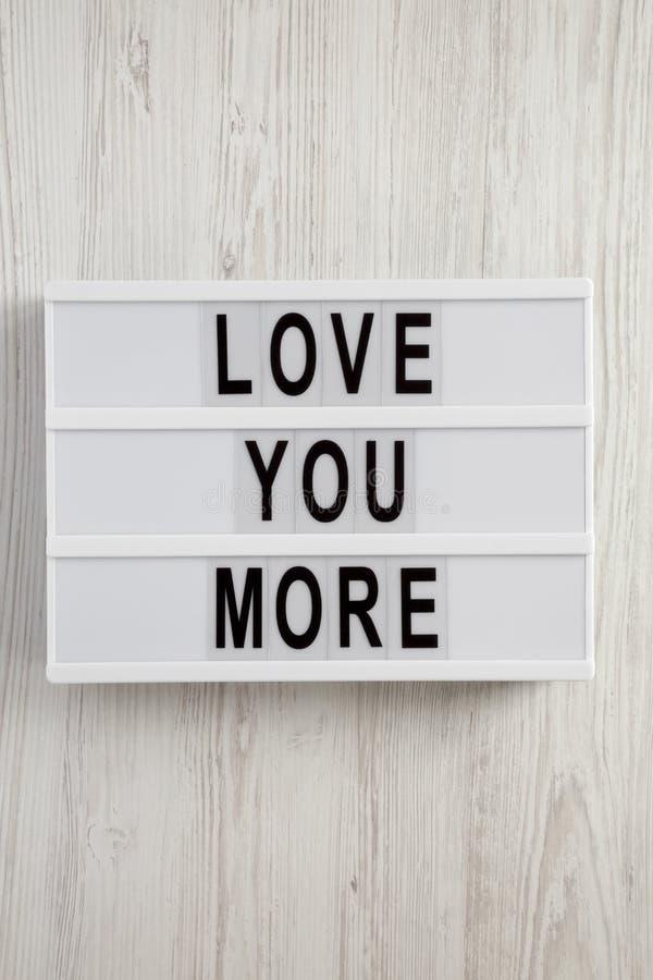 El tablero moderno con el texto 'le ama más 'en un fondo de madera blanco Tarjeta del día de San Valentín ` s día 14 de febrero fotografía de archivo