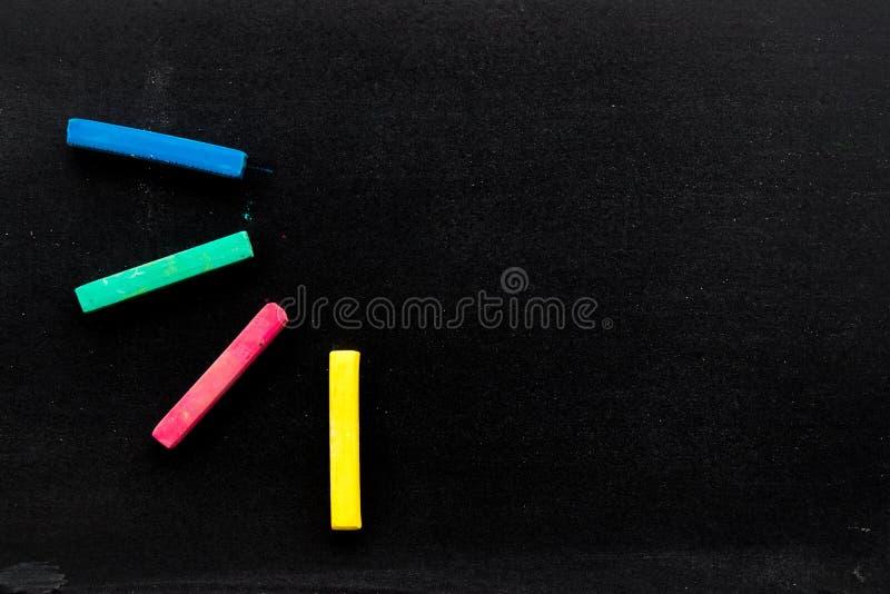 El tablero negro en blanco con color rojo, verde, azul, amarillo marca con tiza detrás imagen de archivo