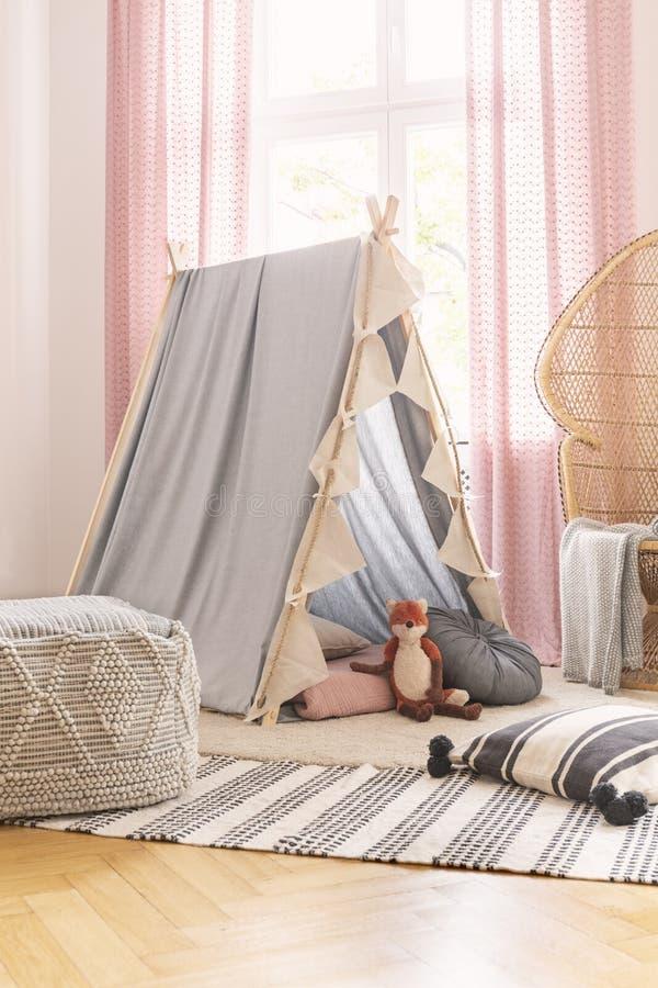 El taburete en la manta modelada cerca de la tienda con el juguete del zorro en el sitio de la muchacha con rosado cubre y soport fotos de archivo libres de regalías