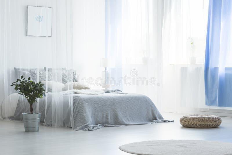 El taburete y la planta cerca del toldo acuestan en dormitorio blanco y azul simple fotografía de archivo