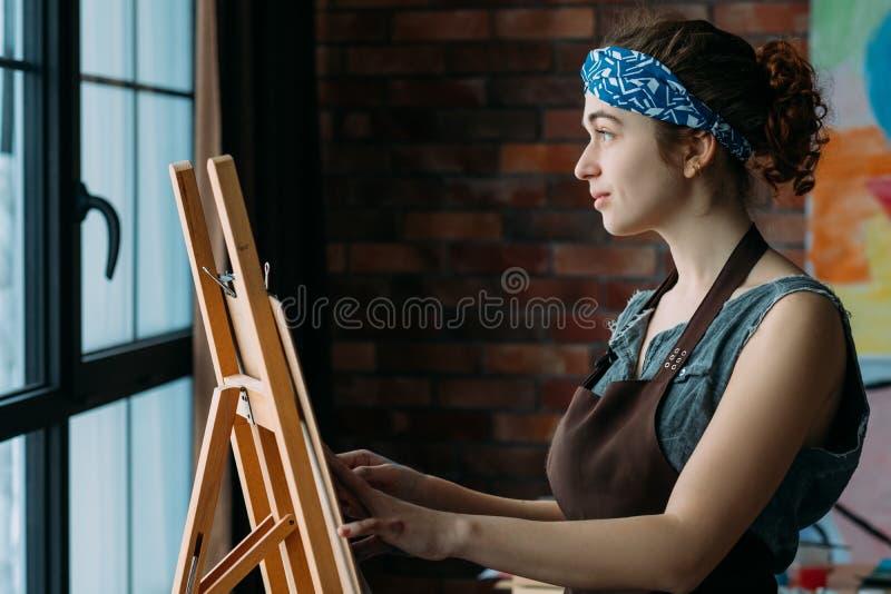 El talento inspiró la pintura femenina del caballete del artista imagenes de archivo