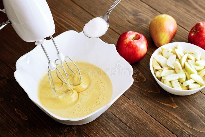 El talud o la pasta de mezcla para la Apple-pera se apelmaza o mollete o crepe Ciérrese para arriba en ingredientes de madera de  imagenes de archivo