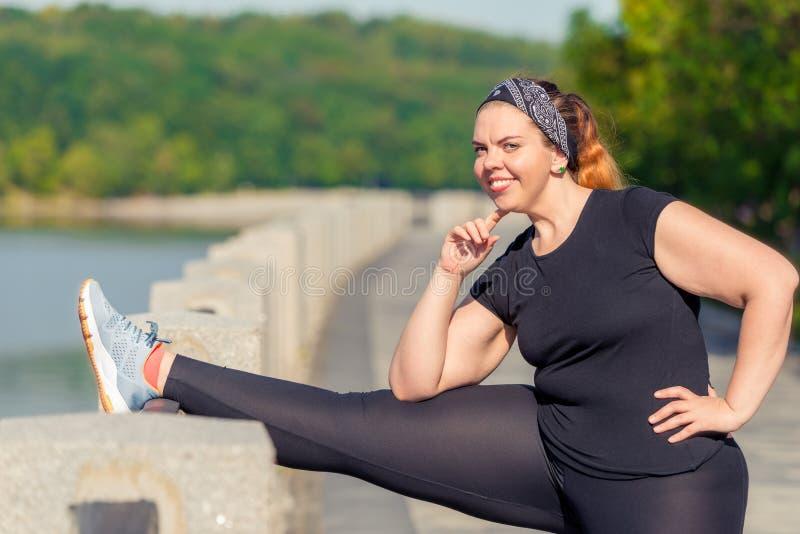 el tamaño extra grande del retrato de la mujer realiza estirar ejercicios en el terraplén en un parque de la ciudad fotografía de archivo libre de regalías
