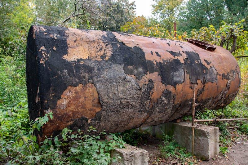 El tanque de agua dilapidado viejo cubierto con las manchas de la pintura negra lamentable fotos de archivo libres de regalías