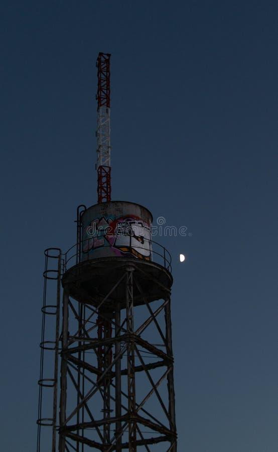 El tanque de agua viejo con la antena y pintada delante de la luna fotos de archivo libres de regalías