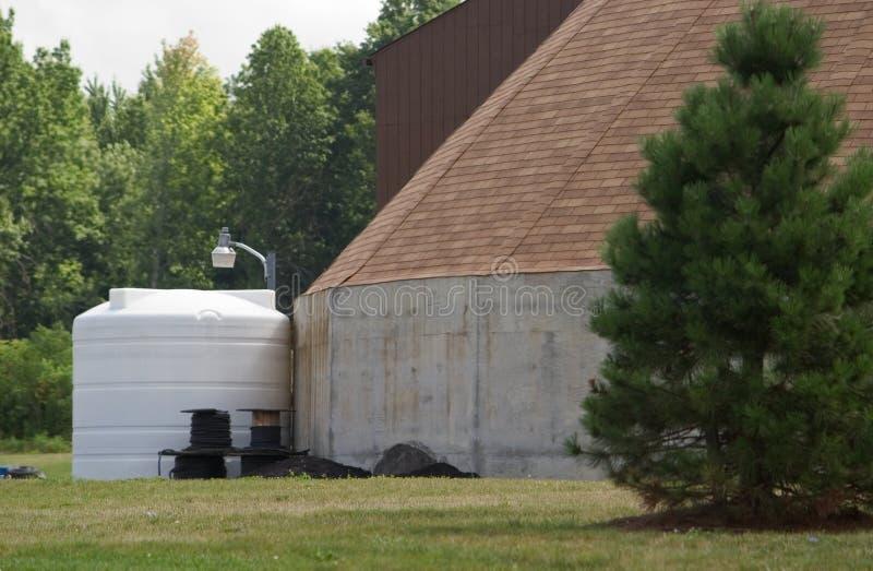 El tanque de almacenaje al lado del edificio imagen de archivo
