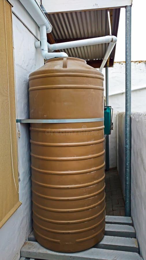 El tanque de almacenamiento del agua de lluvia en área montada sequía imagen de archivo