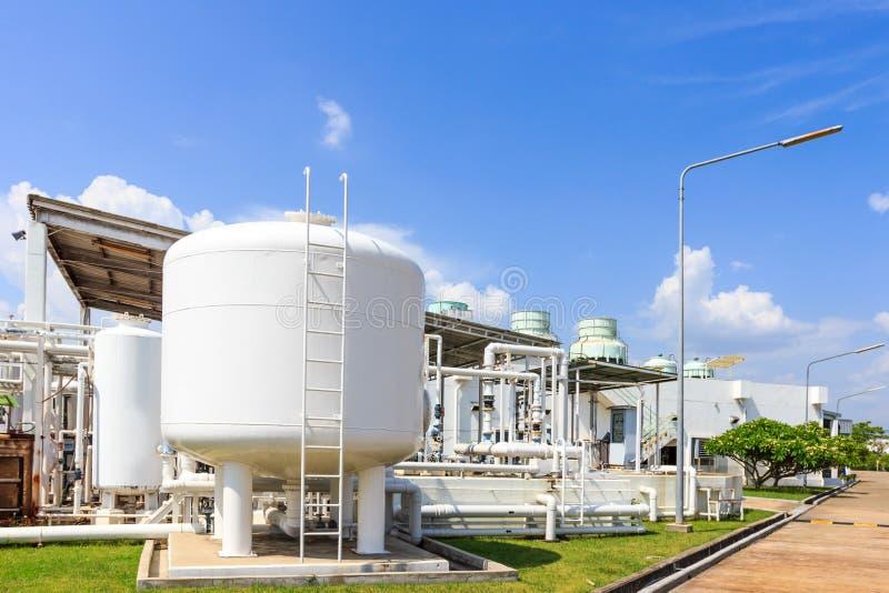 El tanque de la química en fábrica con el cielo azul imagenes de archivo