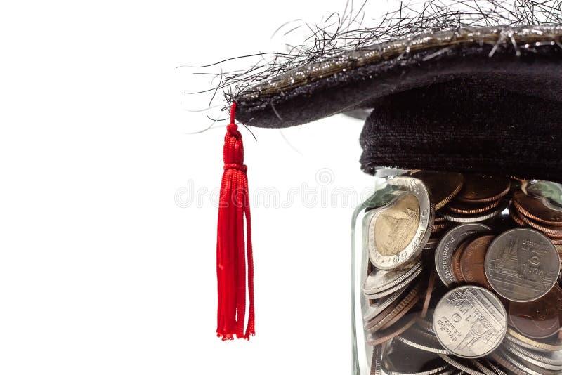 El tarro de cristal de la moneda del dinero con el casquillo académico cuadrado fotografía de archivo