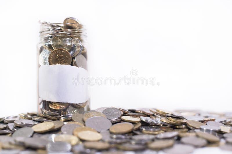 El tarro de cristal llenó de las monedas en un grupo de monedas imágenes de archivo libres de regalías