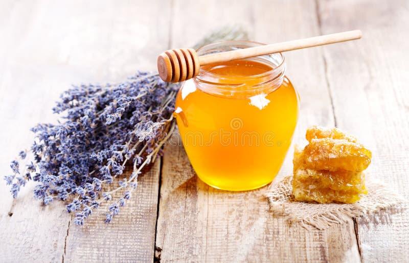 El tarro de miel con el panal y el lavander florece imagen de archivo libre de regalías