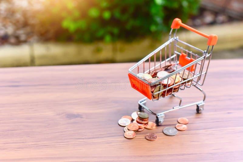 El tarro de Mini Shopping Cart o de la carretilla y del vidrio llenó de las monedas aisladas en una tabla en cuanto a comercio al fotografía de archivo